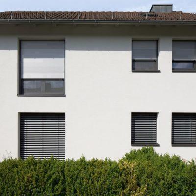 Rollladen als Sonnenschutz an einem weißen Haus